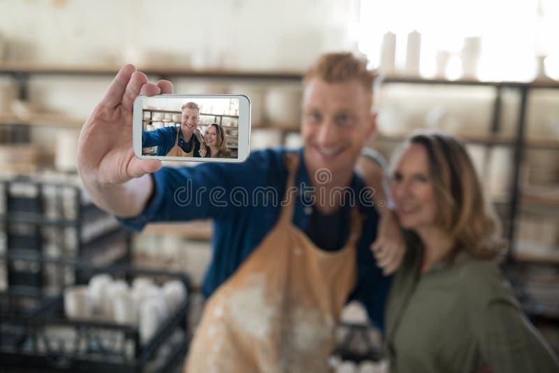 Man och kvinnlig keramiker som tar selfie med mobiltelefonen royaltyfria bilder
