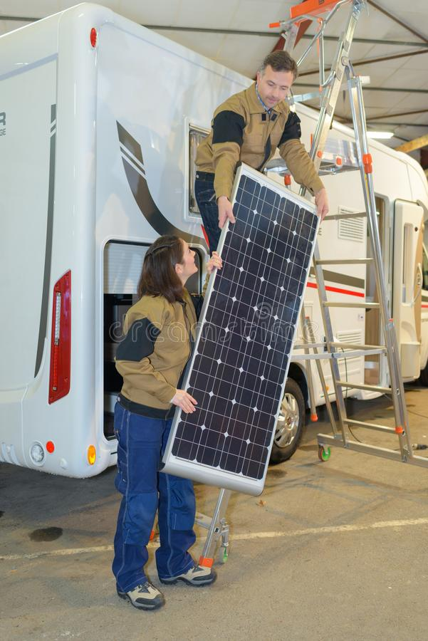 Man och kvinnlig som sätter solpaneler i tak royaltyfria foton
