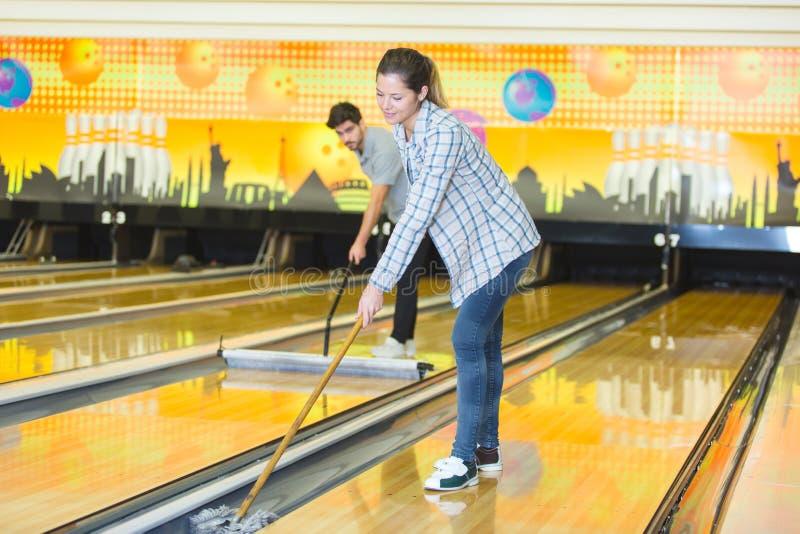 Man och kvinnliga arbetare som gör ren bowlingbanor arkivbilder