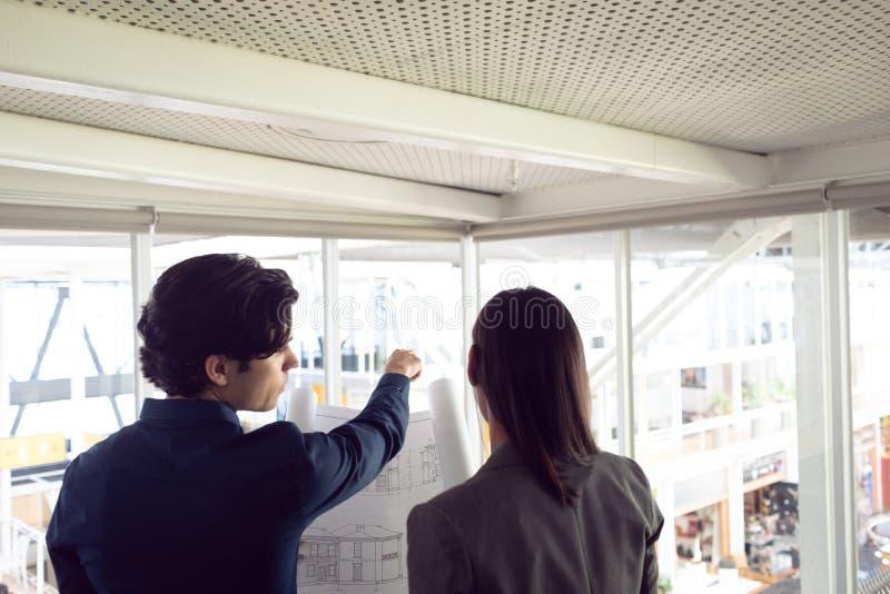 Man och kvinnliga arkitekter som i regeringsställning diskuterar över ritning arkivbilder