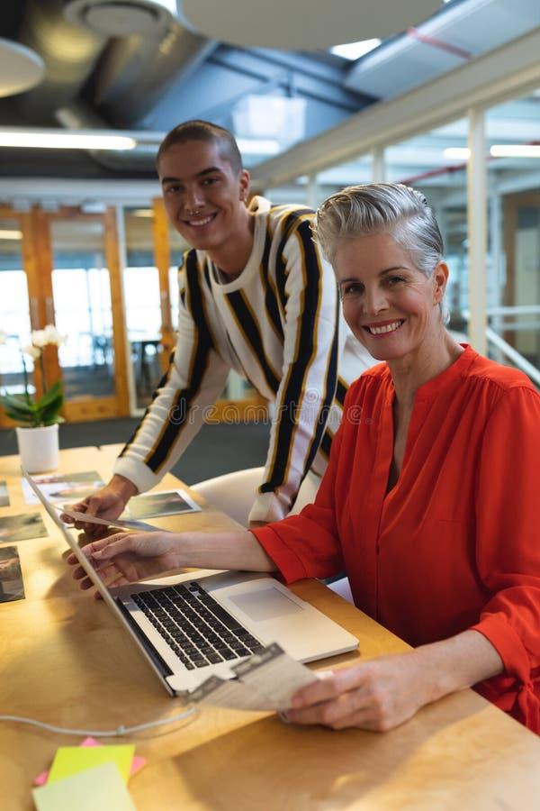 Man och kvinnliga grafiska formgivare som i regeringsställning diskuterar över fotografier på skrivbordet royaltyfri bild