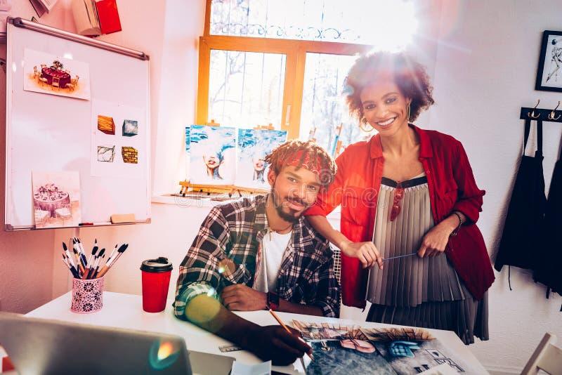 Man och kvinnliga inreformgivare som tillsammans känner gladlynt arbete royaltyfri fotografi