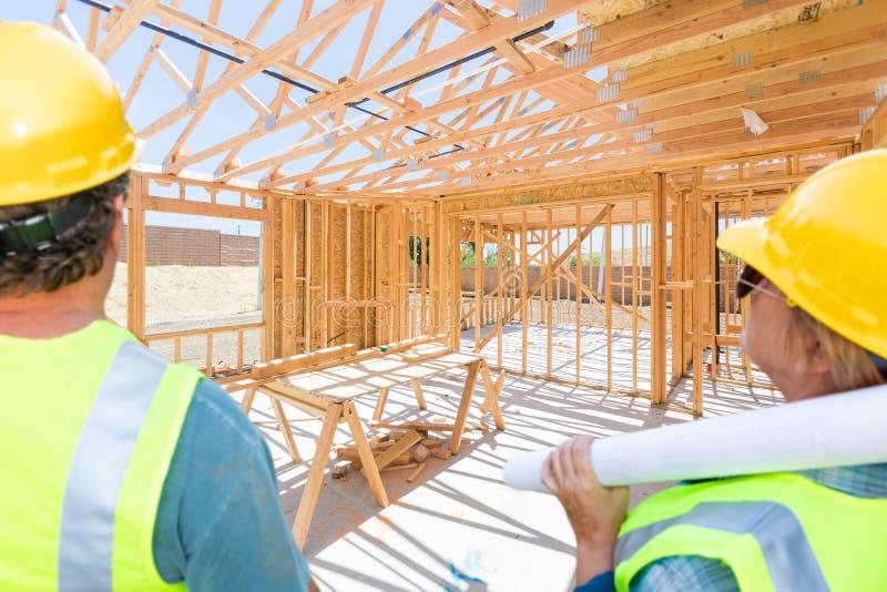 Man och kvinnliga leverantörer som förbiser det nya huset som inramar på konstruktionsplatsen royaltyfria bilder