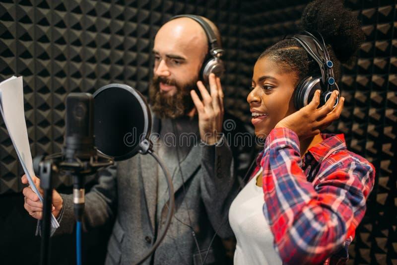 Man och kvinnliga sångare i anteckna studio för ljudsignal royaltyfria bilder