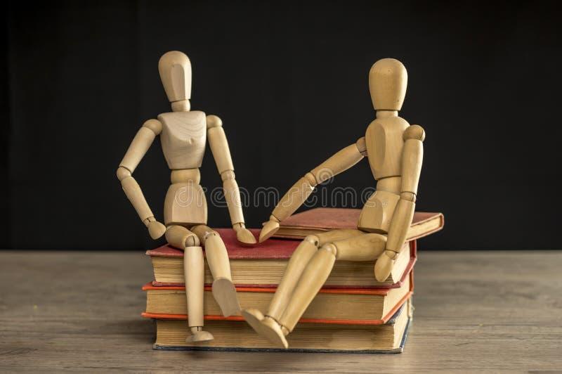 Man och kvinnliga träskyltdockor som sitter på böcker arkivfoto
