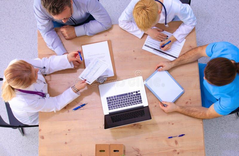 Man- och kvinnligdoktorer som arbetar på rapporter i medicinskt kontor arkivbilder