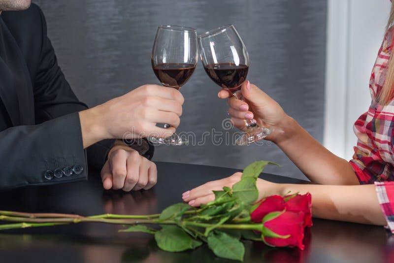 Man och kvinnligt rosta med exponeringsglas av rött vin på restaurangtabellen med röda rosa blommor arkivfoton