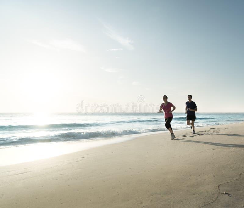 Man och kvinnor som kör på den tropiska stranden på solnedgången royaltyfri foto