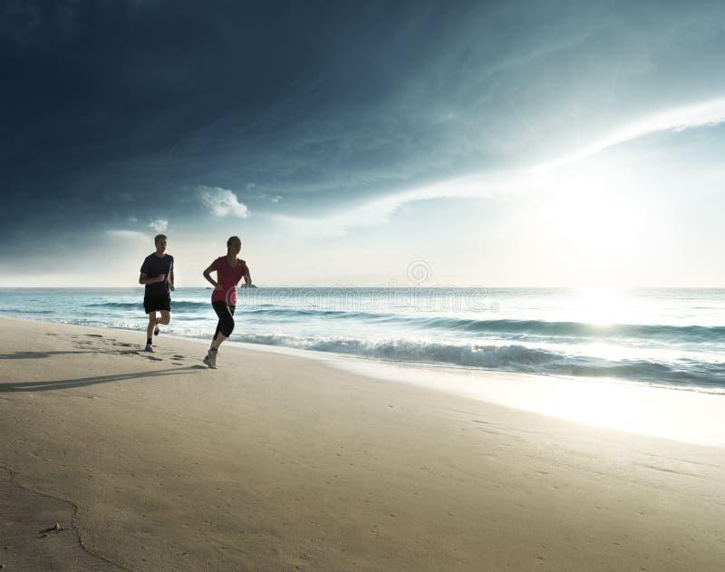 Man och kvinnor som kör på den tropiska stranden på solnedgången arkivbilder