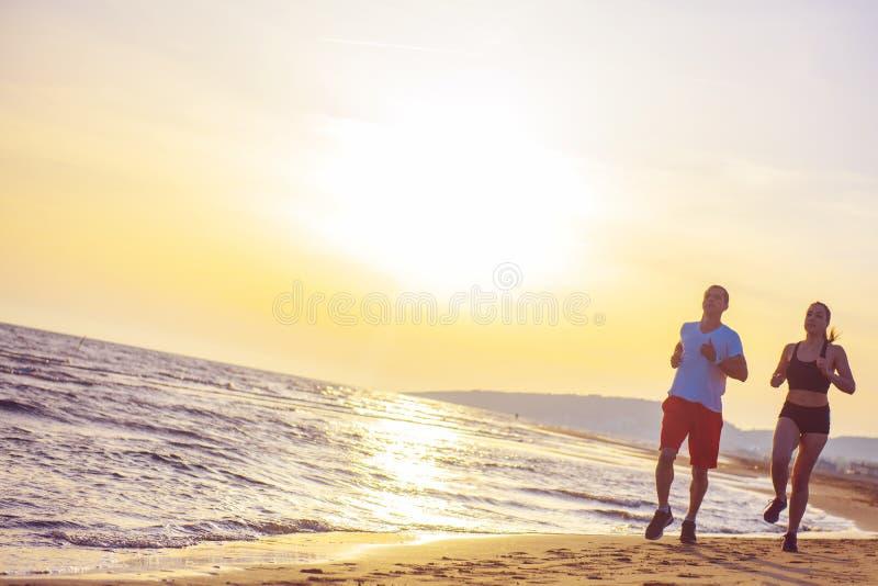 Man och kvinnor som kör på den tropiska stranden på solnedgången arkivfoto