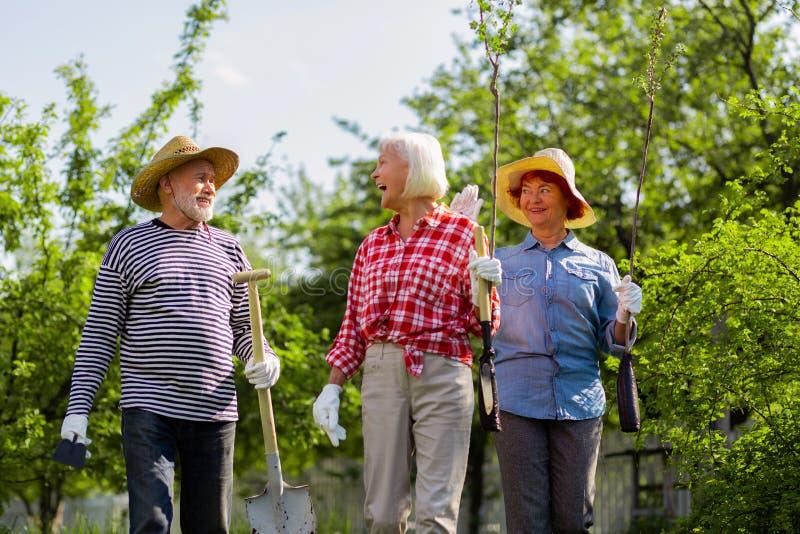 Man och kvinnor som skrattar, medan gå för att plantera träd tillsammans royaltyfri fotografi