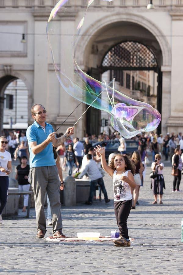 Man- och liten flickabarn med stora såpbubblor arkivfoton