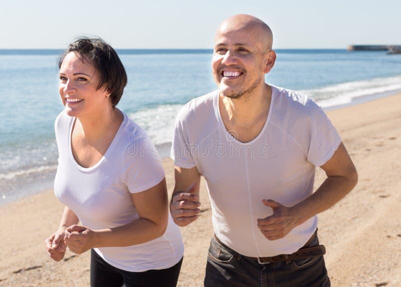 Man och medelålders kvinnaspring på stranden royaltyfria foton