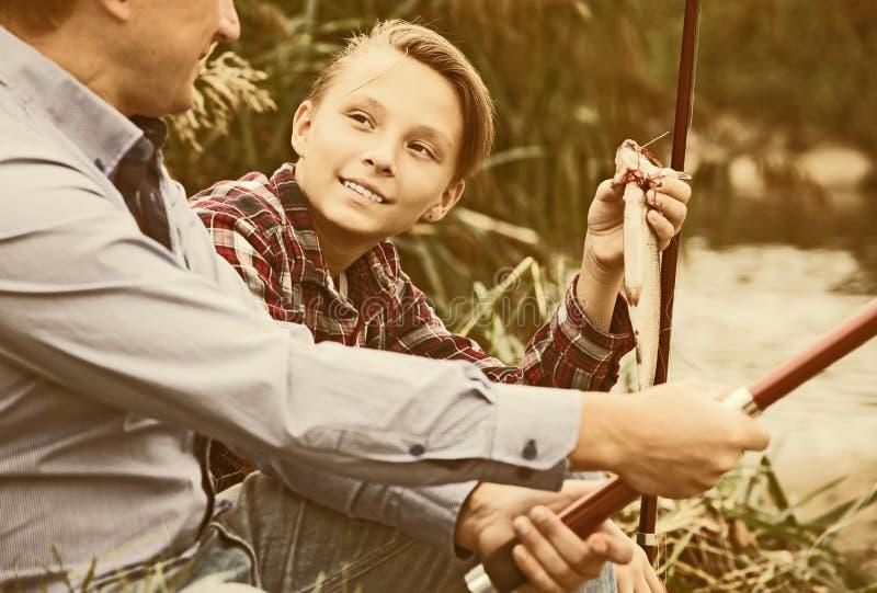 Man och pojke som tillsammans fiskar på den sötvattens- floden fotografering för bildbyråer