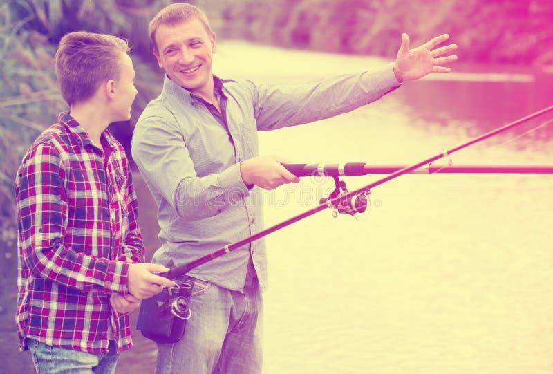 Man och pojke som tillsammans fiskar på den sötvattens- sjön fotografering för bildbyråer