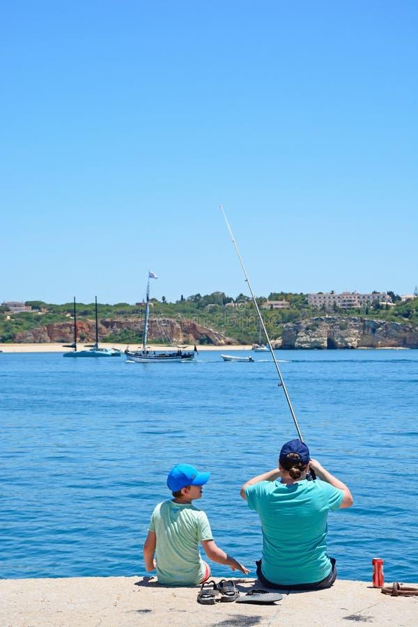 Man- och pojkefiske, Portimao royaltyfri bild