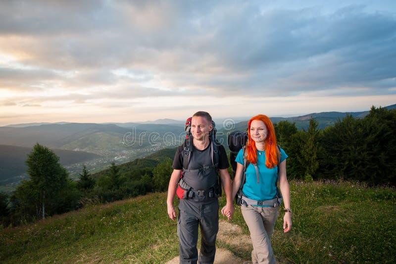 Man och rödhårig kvinna på vägen i bergen royaltyfria bilder
