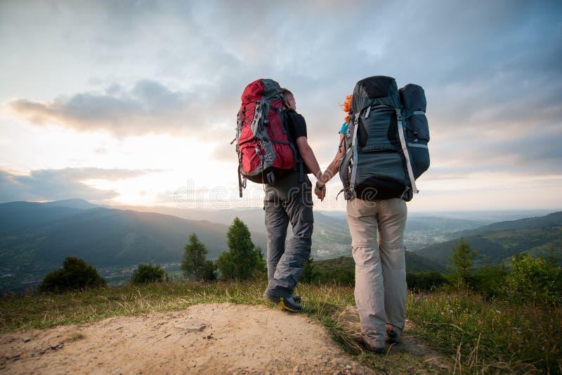Man och rödhårig kvinna på vägen i bergen arkivfoto