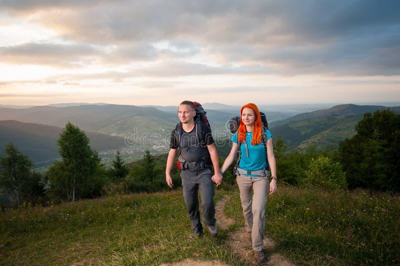 Man och rödhårig kvinna på vägen i bergen royaltyfri bild