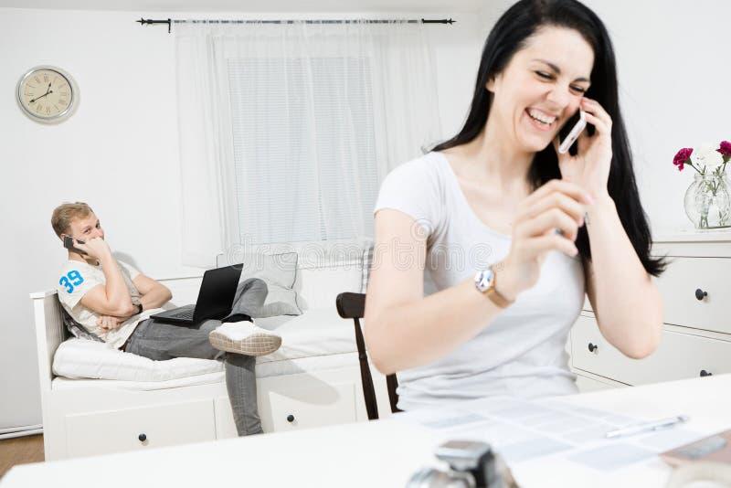 Man och skrattakvinna som kallar med mobiltelefoner arkivfoto