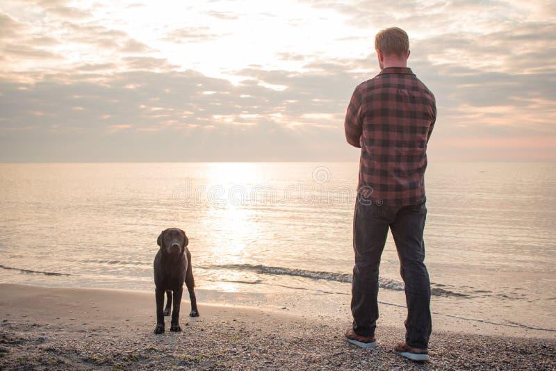 Man och svart hund på stranden royaltyfria bilder