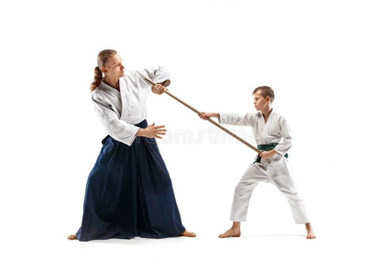 Man och tonårig pojke som slåss med träsvärd på Aikidoutbildning i kampsportskola royaltyfria foton