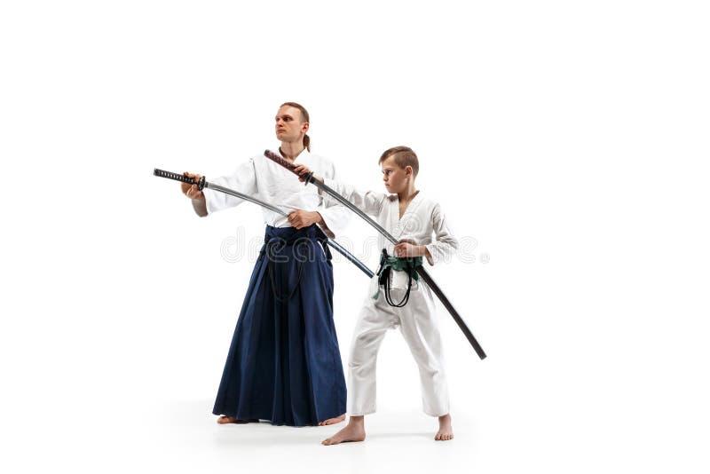 Man och tonårig pojke som slåss på aikidoutbildning i kampsportskola royaltyfria bilder