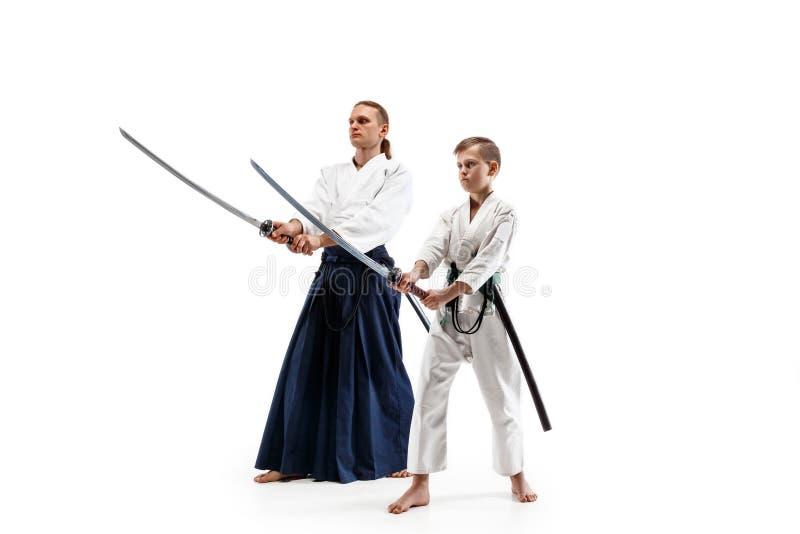 Man och tonårig pojke som slåss på aikidoutbildning i kampsportskola fotografering för bildbyråer