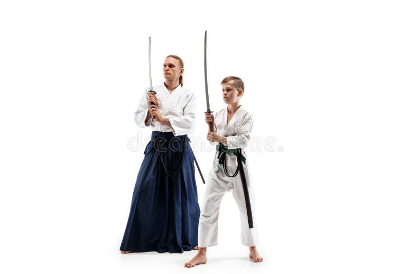 Man och tonårig pojke som slåss på aikidoutbildning i kampsportskola royaltyfri bild
