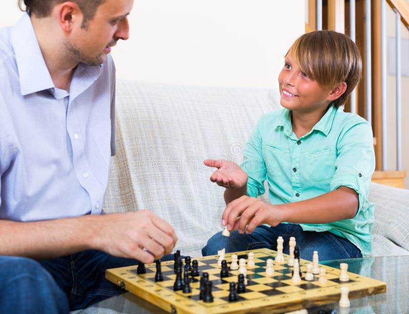 Man- och tonåringson som spelar schack royaltyfria foton