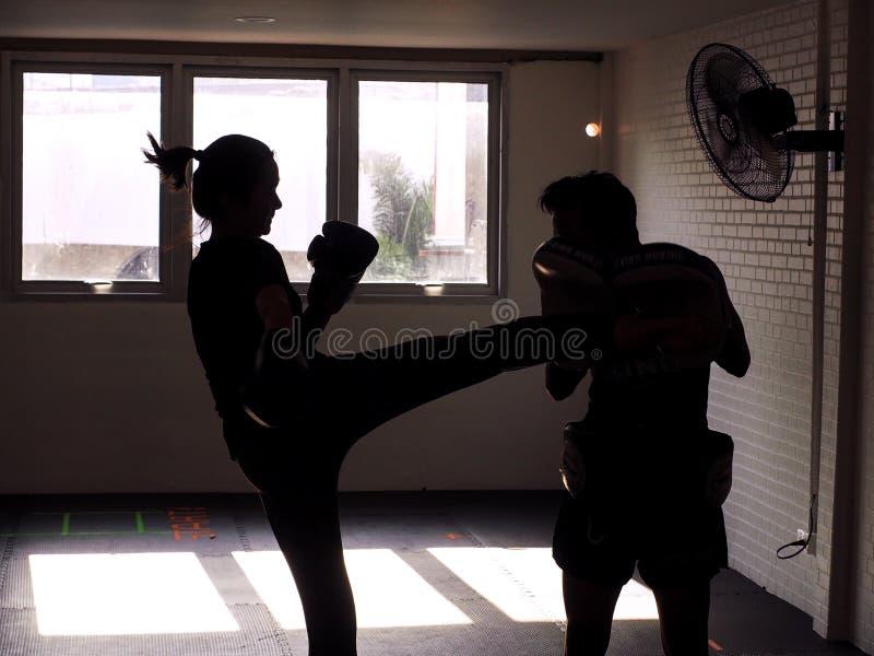 Man och ung kvinna som tillsammans slåss Kvinnligt praktiserande boxas Färdig kvinna och hennes instruktör Boxing Indoors Stående arkivfoto