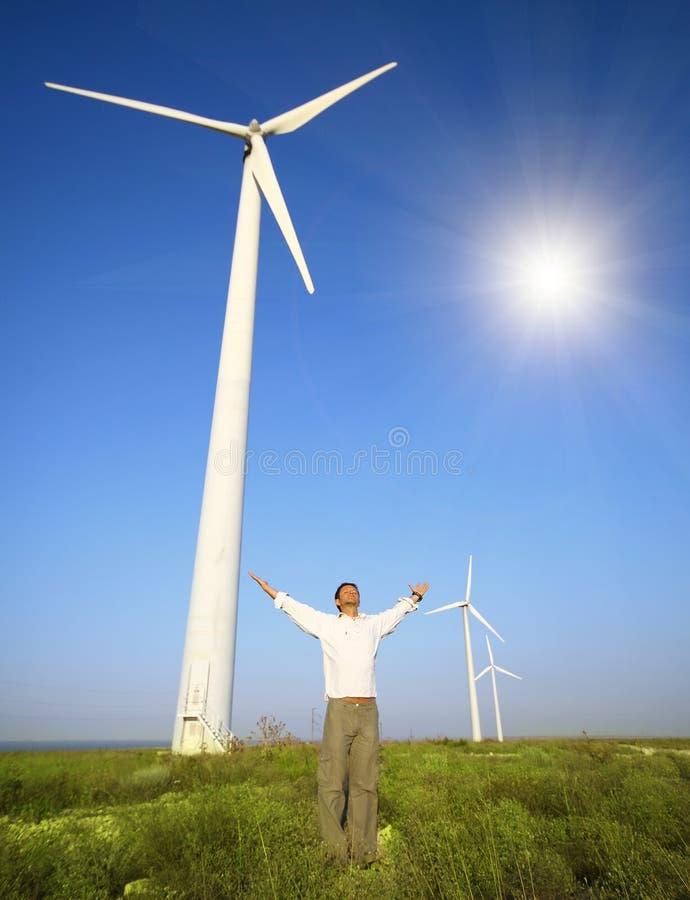 Man- och vindturbiner under himmel royaltyfri fotografi