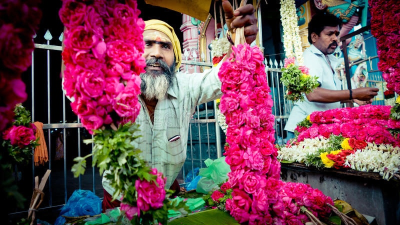 Man offer flowers near the temple India. Bright and red flowers royalty free stock photos