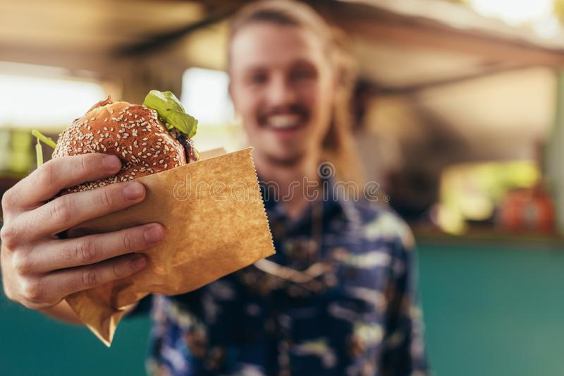 Man offering a food truck burger stock photo