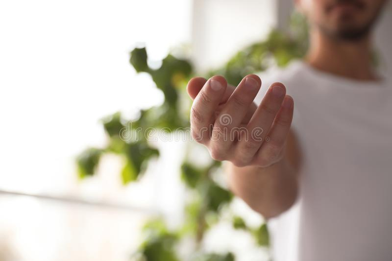 Man offering helping hand on blurred background, closeup. Space for text stock images