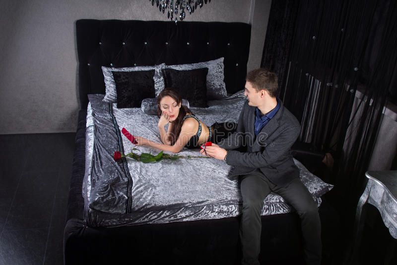 Man Offering a Ring to Girlfriend at the Bedroom stock photography
