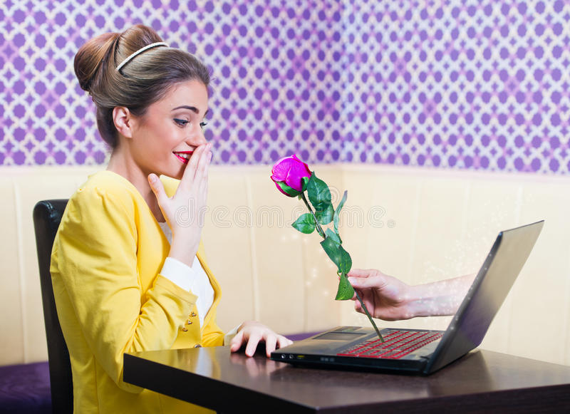 Man offering a rose to a beautiful woman over laptop screen royalty free stock images