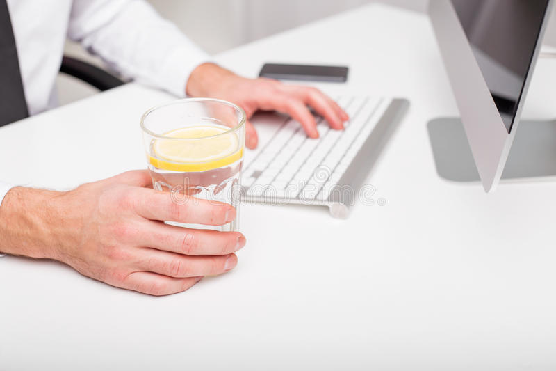 Man at the office drinking lemon water