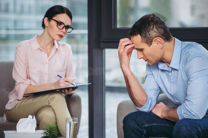 Man in office with female psychologist stock images