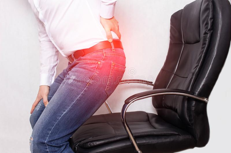 A man in the office holding his back from a chair, the concept of back pain, intervertebral hernia and osteochondrosis royalty free stock photos