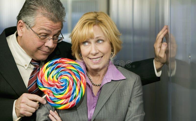 Man in office offers coworker a lollipop. Executive in office offers coworker a big lollipop royalty free stock image