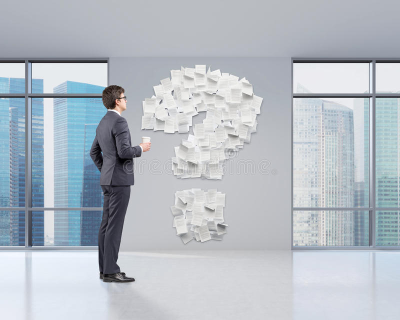 Man in office and question mark. Side view of a businessman holding a coffee cup and looking at a question mark made of papers glued to a wall. 3d rendering royalty free stock image