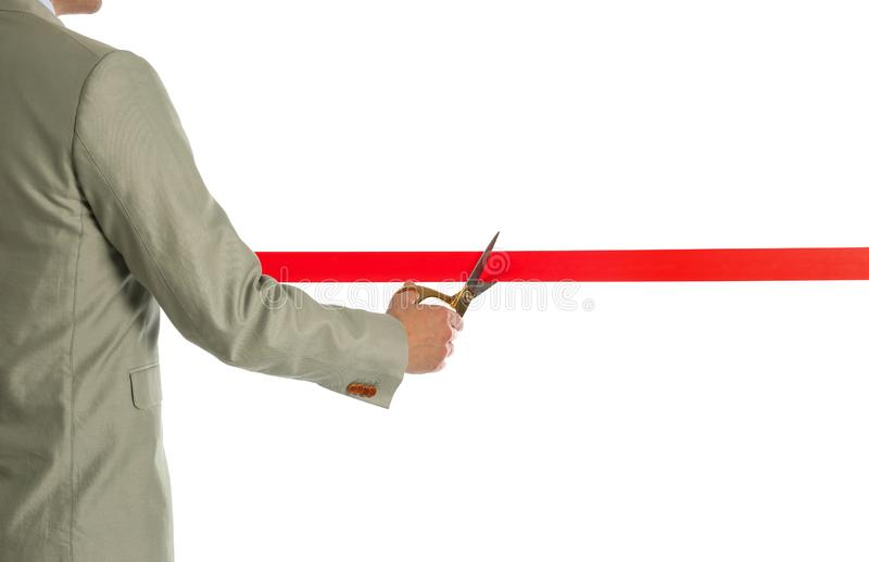 Man in office suit cutting red ribbon, closeup. Man in office suit cutting red ribbon isolated on white, closeup royalty free stock photo