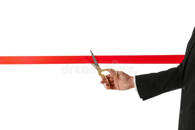 Man in office suit cutting red ribbon isolated on white. Closeup royalty free stock images