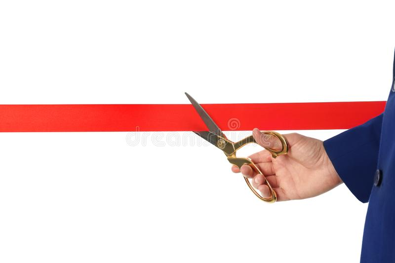 Man in office suit cutting red ribbon isolated on white. Closeup royalty free stock photos