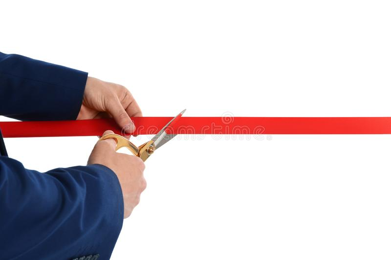 Man in office suit cutting red ribbon isolated on white. Closeup royalty free stock photo