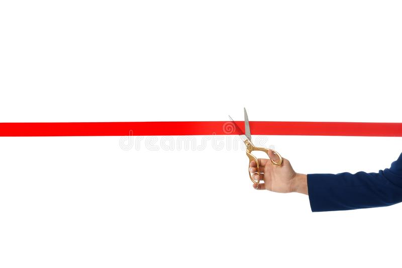 Man in office suit cutting red ribbon isolated on white. Closeup stock photo