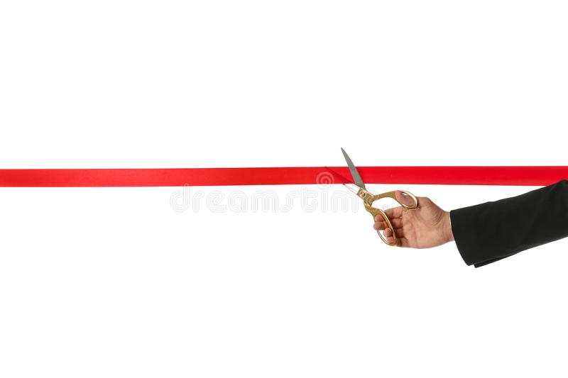 Man in office suit cutting red ribbon isolated on white. Closeup stock images