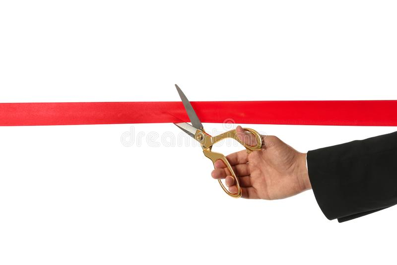 Man in office suit cutting red ribbon isolated on white. Closeup royalty free stock photography