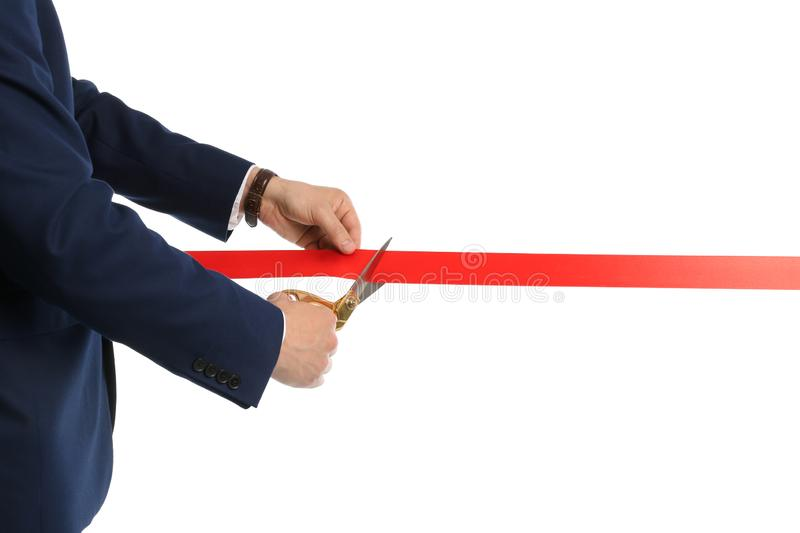 Man in office suit cutting red ribbon, closeup. Man in office suit cutting red ribbon isolated on white, closeup royalty free stock images